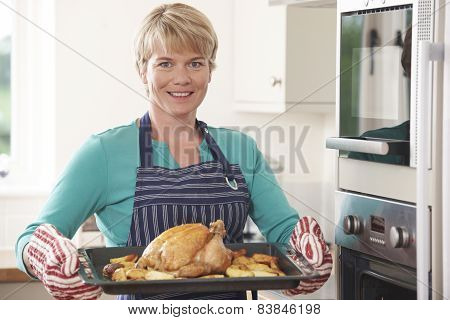 Woman In Kitchen Holding Tray With Roast Chicken