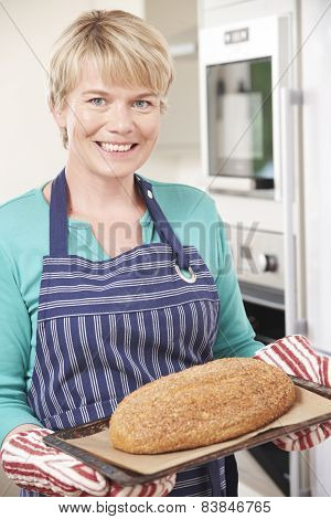 Woman In Kitchen Holding Tray With Home Made Loaf Of Bread