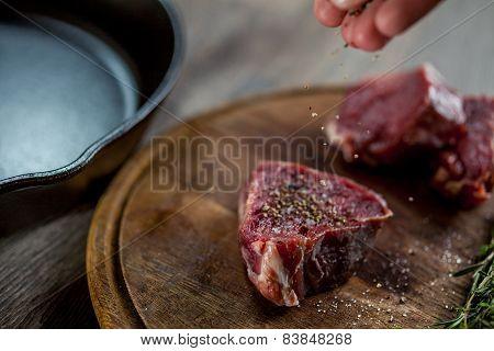 Man seasoning tenderloin steaks with ground pepper