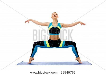 Attractive young woman engaged in pilates on mat