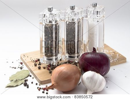 onion, glass mill with pepper, salt and spices on a wooden Board, isolated