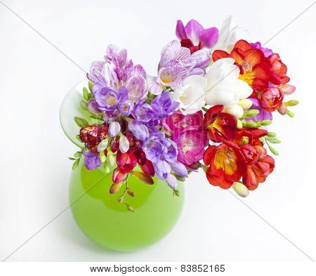 Beautiful Bouquet Of Colorful Freesia In Green Vase On A White Background