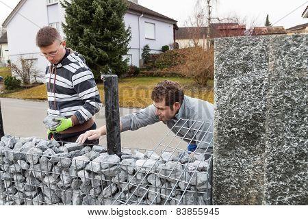 handymen filling gabione with gravel stones