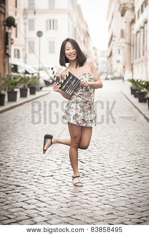 Young Asian Woman Smiling And Showing Clapperboard Urban Scene