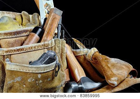 Rugged Leather Carpenters Work Bag With Construction Tools Isolated on Black Background