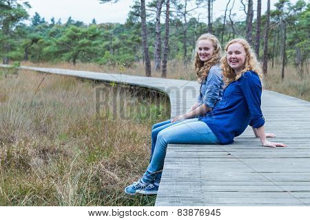 Two sisters sitting on wooden path in forest