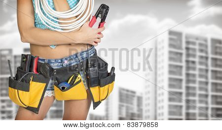 Woman in tool belt holding cable and pliers. Buildings with gray sky as backdrop