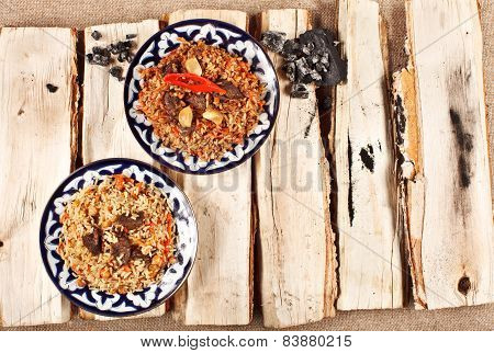Traditional Central Asia Pilaw In Uzbek Plate On Logs