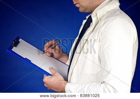 Doctor Writing In His Notebook Isolated On Blue