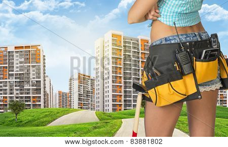 Woman in tool belt stands back. Green hills with road and buildings on background