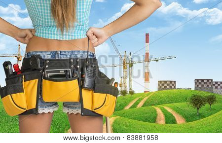 Woman in tool belt stands back. Green hills and cranes with heat power stations on background