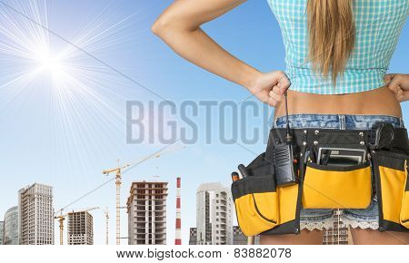 Woman in tool belt stands back. Hands on hip. Building and sky as backdrop