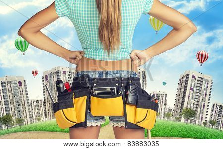 Woman in tool belt stands back, akimbo. Cropped image. Green hill, buildings as backdrop