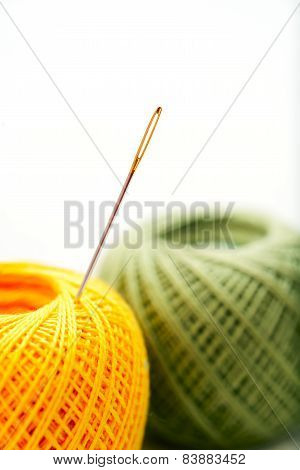 Close-up needle in color clews on white background