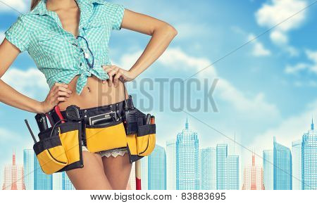 Woman in tool belt stands back, hands on hips. Cropped image. Wire-frame buildings as backdrop
