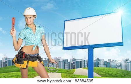 Woman in tool belt holding wrench and two hoses. Green hills, road, buildings, billboard as backdrop