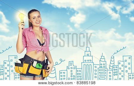 Woman in tool belt holding light bulb. Sketch buildings, chimneys as backdrop