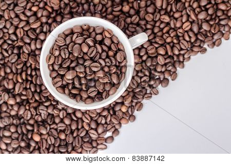ceramic cup on a pile of roasted coffee beans.