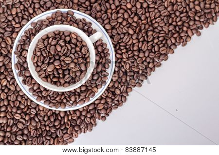 ceramic cup and saucer on a pile of roasted coffee beans.