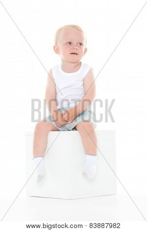 Unhappy Baby Boy Sits On Cube.