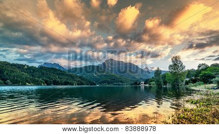Vibrant Intense Sunset Landscape On Lake And Mountain Background.