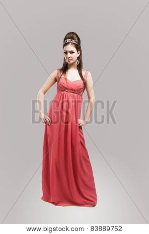 Portrait Of Beautiful Sensual Young Female With Crown Wearing Fashionable Pink Dress. Isolated Again