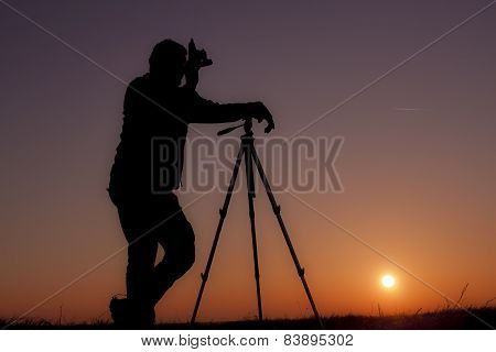 photographer with old camera and tripod in sunset