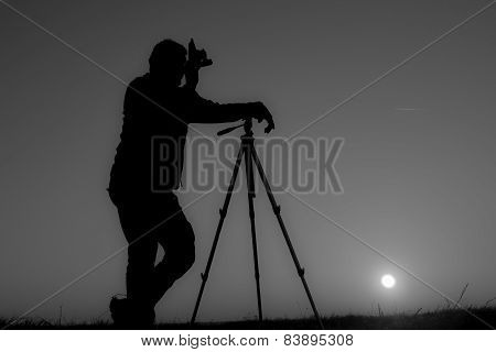 photographer with old camera and tripod in twilight