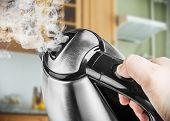 picture of kettles  - Stainless Steel Electric Kettle in hand on the background of the kitchen - JPG