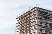 stock photo of scaffold  - Unfinished building with scaffolding against blue sky background - JPG
