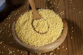 image of millet  - Millet in a wooden bowl and spoon on a wooden background - JPG