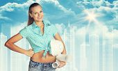 stock photo of framing a building  - Woman in shirt and shorts holding white helmet and rolls of paper - JPG
