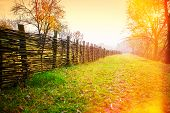 stock photo of wooden fence  - wooden wicker fence in the countryside orange daylight - JPG