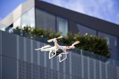 stock photo of drone  - Radio controlled quadcopter drone flying in the city - JPG