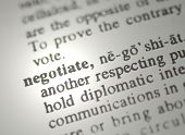 image of bartering  - The word negotiate from the dictionary showing a shallow depth of field - JPG