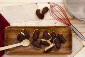 foto of eclairs  - Eclairs on a table among kitchen accessories - JPG