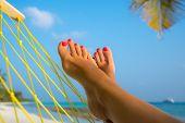 stock photo of foot  - woman feet in hammock on the beach - JPG