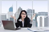 stock photo of confuse  - Young asian female worker doing her job in the office and looks confused - JPG