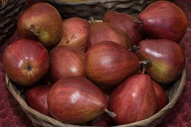 stock photo of anjou  - Red Anjou Pears in a wicker basket at a Tucson Farmers Market.