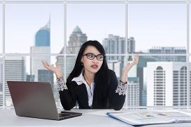 picture of confusing  - Young asian female worker doing her job in the office and looks confused - JPG