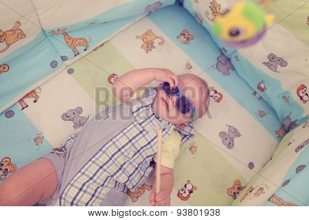 Playful Kid In His Bed With Sunglasses