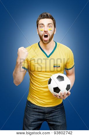 Colombian fan holding a soccer ball celebrates on blue background