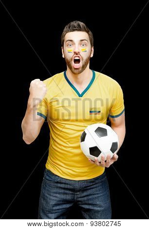 Colombian fan holding a soccer ball celebrates on black background