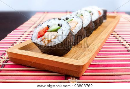 Sushi on a wooden platter and bamboo mat