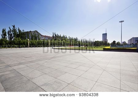 long empty footpath in modern city square with skyline.