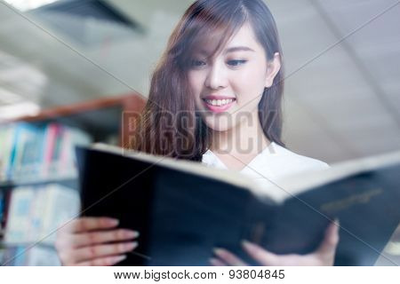 beautiful asian female student reading book in library
