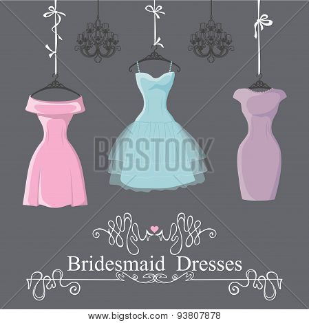 Three short bridesmaid dresses hang on ribbons