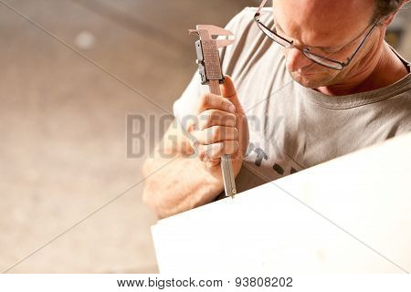 Carpenter Measuring A Board With Calipers