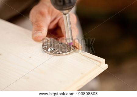 Focus On A Driver Bit Screwing A Wooden Board
