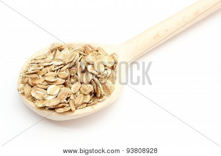 Heap Of Rye Flakes With Wooden Spoon On White Background